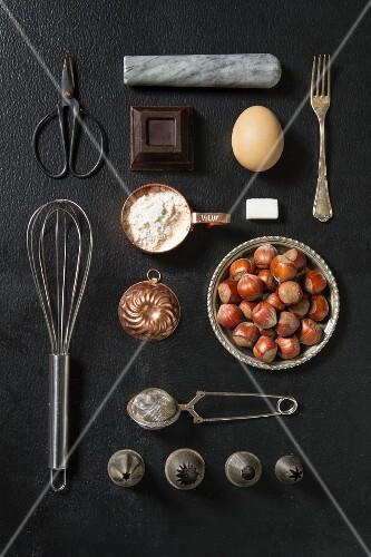 An arrangement of kitchen utensils and baking ingredients on a dark surface