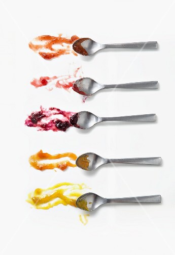 Five different jams on spoons on a white surface