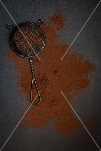 A sieve and cocoa powder on a grey surface (seen from above)