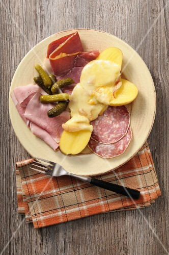 Raclette potatoes with various types of cold meat and gherkins