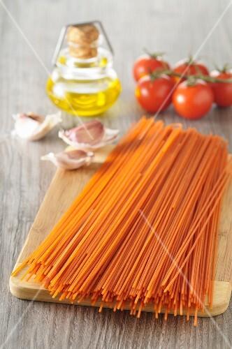 Uncooked tomato spaghetti on a wooden board