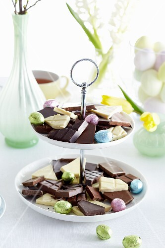 Pieces of chocolate and foil-wrapped Easter eggs on a cake stand