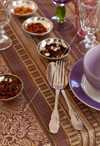 Table elegantly set with purple and gold tablecloth, silver cutlery and silver dishes