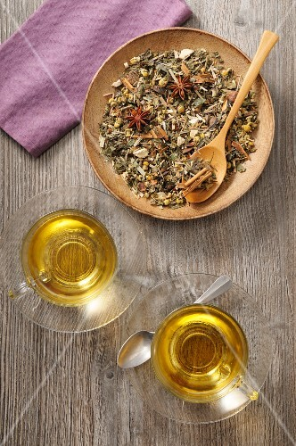 Herb tea with spices: loose leaf tea on a plate and brewed in glass cups