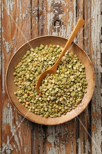 Split peas in a wooden bowl with a wooden spoon (seen from above)