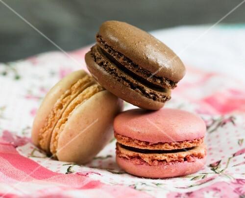 Three macaroons: chocolate, vanilla and raspberry (close-up)