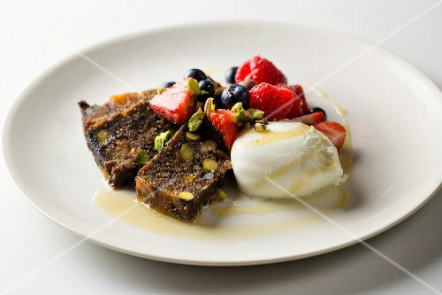 Two slices of fig and pistachio nut cake with ice cream and berries