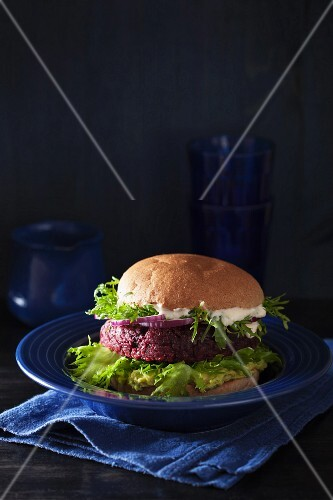 A veggie burger with a beetroot patty, avocado spread and vegan sauce