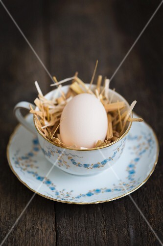 An egg in a teacup of straw on a wooden floor