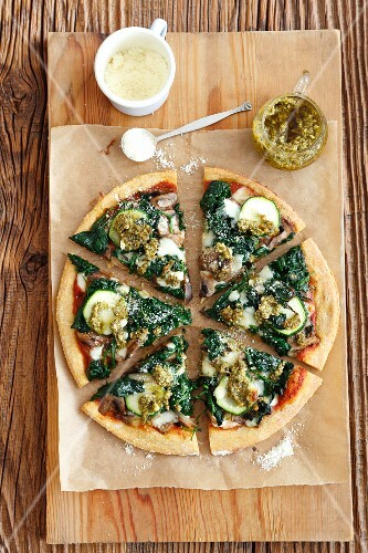 A vegetarian pizza topped with spinach, mushrooms and courgette
