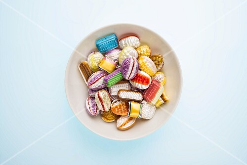 A mixture of sweets in a white bowl on a blue surface seen from above