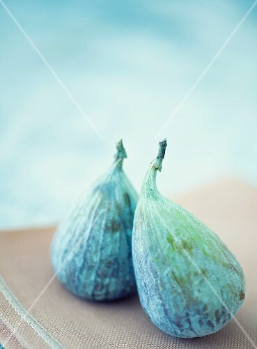 Two figs on a brown tea towel against a light blue background