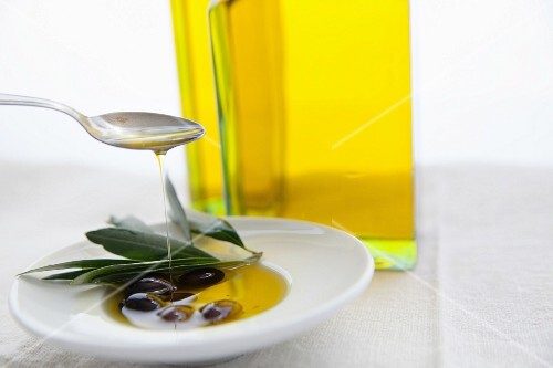 Olive oil being poured over lives in a bowl