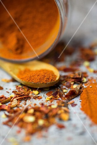 An arrangement of spices with chilli powder and chilli flakes