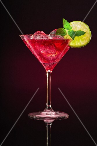 Aping cocktail in a glass garnished with a lime slice and a sprig of mint against a dark background