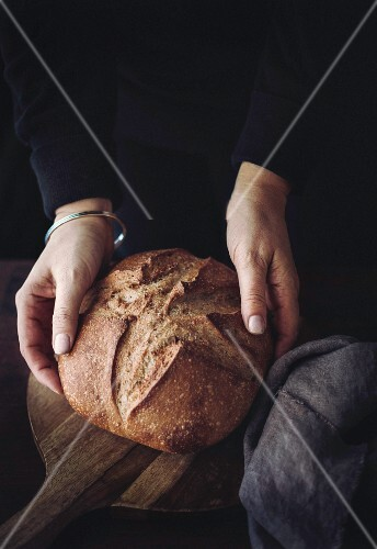 Hands holding a loaf of bread