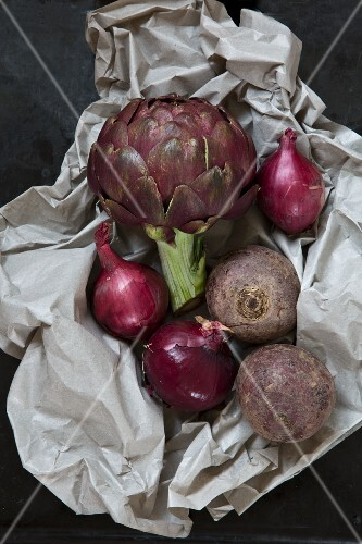 An arrangement of vegetables featuring artichoke, red onions and beetroot on piece of paper
