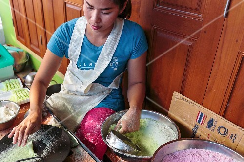 A young woman preparing sweets made from rice flour and coconut, Thailand