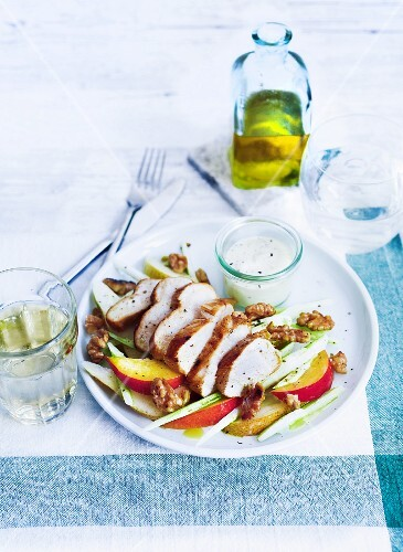 Marinated chicken breast on a peach salad with spring onions and walnuts