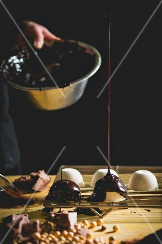 A confectioner glazing pralines with melted chocolate