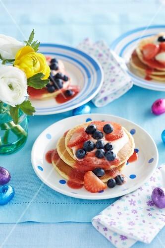 Pancakes with cream, strawberry sauce and berries for Easter