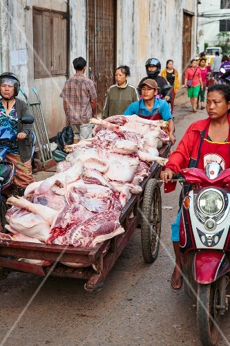 A man transporting fresh meat at a market in Vientiane, Laos
