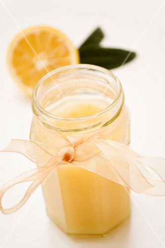 A jar of lemon curd with a chiffon ribbon