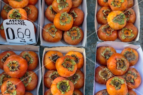 Persimmons in cardboard boxes at a market in Athens, Greece