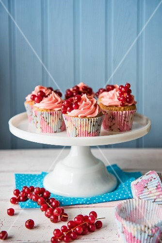 Cupcakes with pink cream and fresh redcurrants on a cake stand