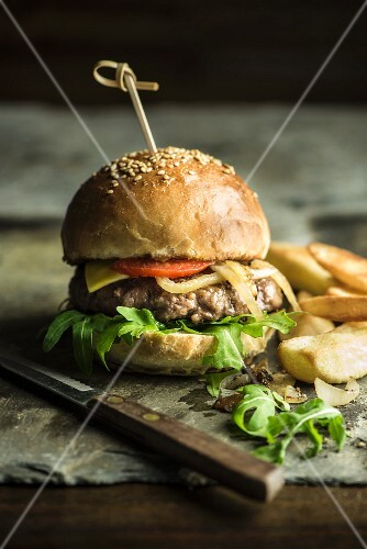 A burger with chips and a rocket salad