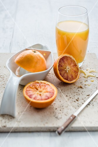 Freshlu squezed orange juice in a glass next to halved oranges
