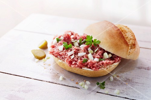 A roll with raw minced meat, onions and gherkins