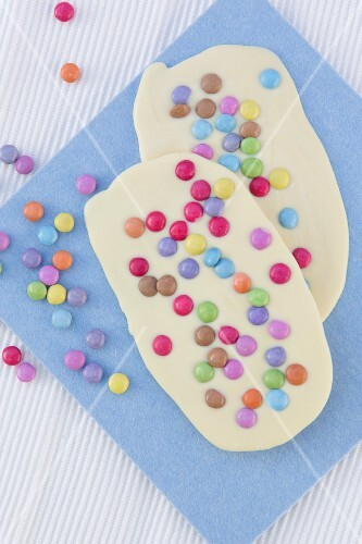 Two bars of white chocolate with colourful chocolate beans