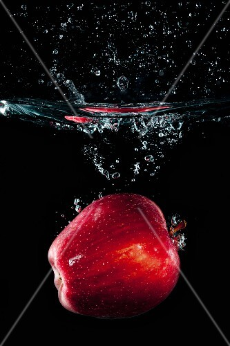 A red apple falling in water with a splash