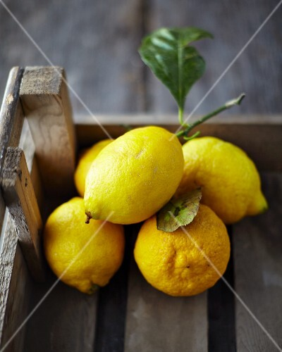Lemons with leaves in a crate on a wooden surface