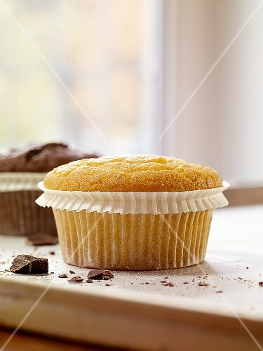 Two different muffins in front of a window