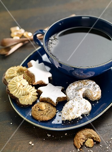 Various Christmas biscuits on a plate with a cup of tea
