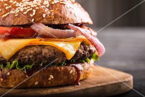 A cheeseburger with tomatoes and onions (close-up)