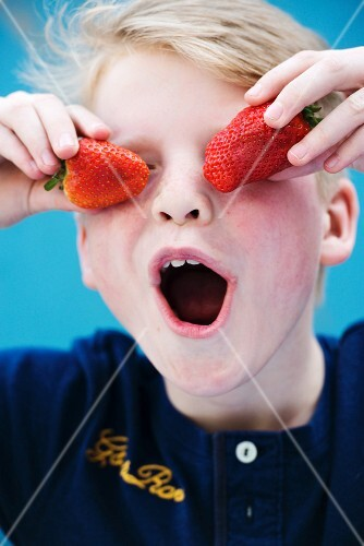 A boy holding two strawberries in front of his eyes