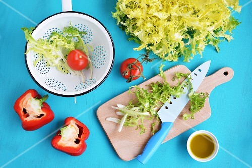 Various salad ingredients: frisee lettuce, tomatoes, peppers and olive oil
