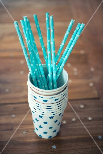 Blue straw in a stack of paper cups decorated with stars