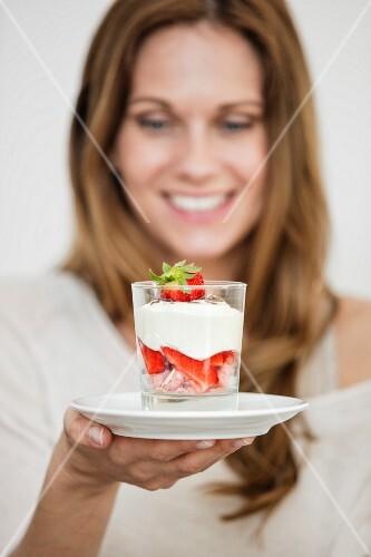 A woman holding a glass of strawberry tiramisu