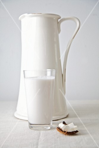 Coconut milk in a glass with a white jug behind it