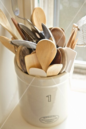 Wooden and metal spoons in a ceramic pot on a kitchen window sill