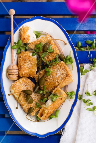 Fried feta cheese in a sesame seed coating with honey, caper fruits and basil