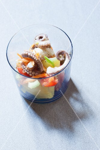 Octopus salad with potatoes and tomatoes in a glass