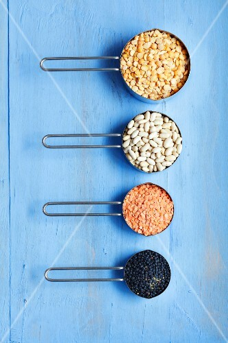 an arrangement of yellow peas, white beans, red and black lentils