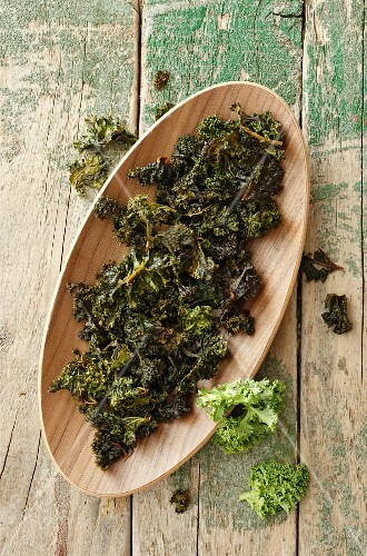Kale chips on a wooden plate