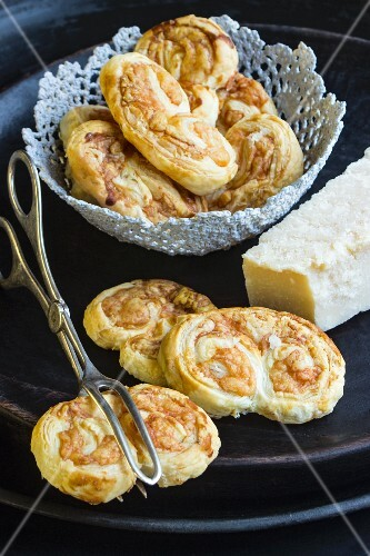 Savoury puff pastries with Parmesan cheese on a black plate with a pair of pastry tongs