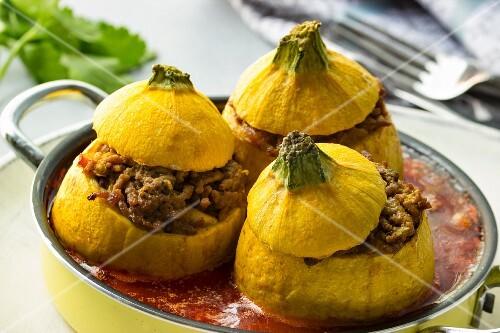 Mit Hackfleisch gefüllte gelbe Zucchini mit Tomatensauce und Besteck
